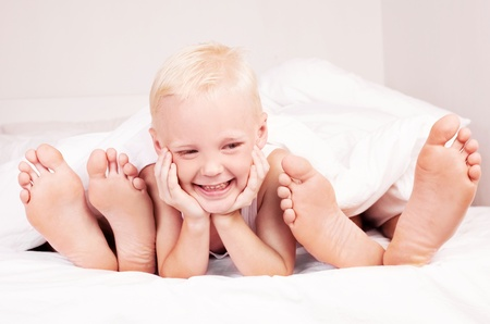happy boy with his mother and father under the blanket in  bed at home   photo