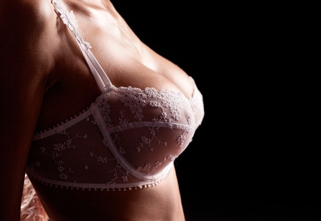 sexy breast: breast of a beautiful young woman wearing white bra, isolated on black background