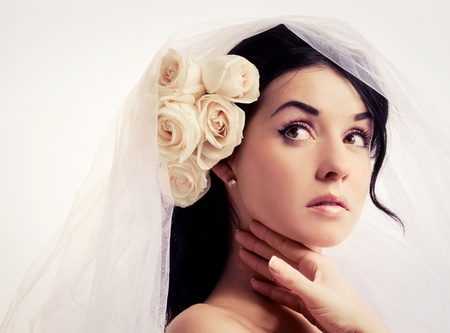 beautiful young brunette woman with a veil and roses in her hair photo