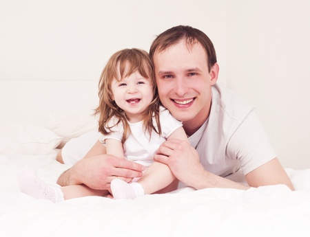 happy family,  father and daughter embracing and laughing in bed at home Stock Photo - 12989780