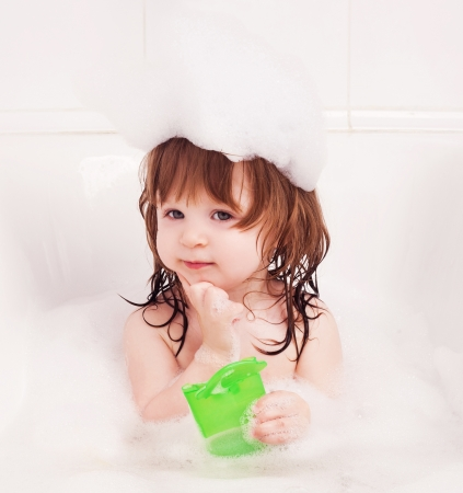 thoughtful one year old girl taking a bath with foam and holding shampoo in her hands