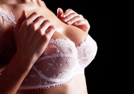 beaux seins: du sein et les mains d'une jeune femme portant un soutien-gorge blanc magnifique avec de la broderie, isolé sur fond noir accent sur la main
