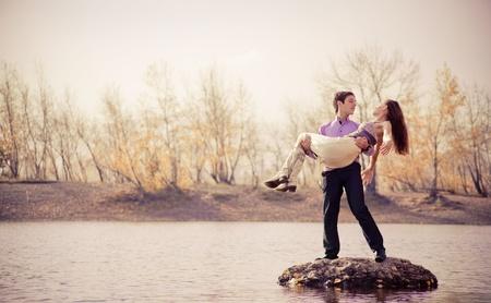 秋の公園で屋外、幸せな若いカップルの低コントラストの肖像画