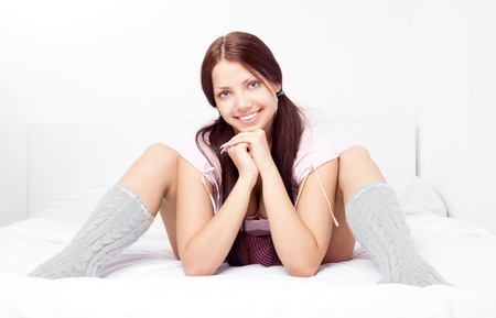portrait of a pretty girl wearing socks and pajamas in bed at home  Stock Photo