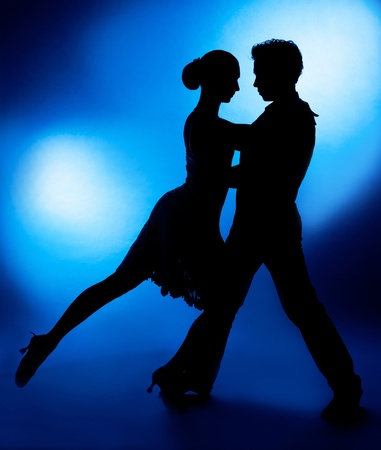 ballroom dancing: A silhouette of a couple dancing against blue studio background Stock Photo