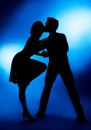 A silhouette of a couple dancing and kissing, against blue studio background photo