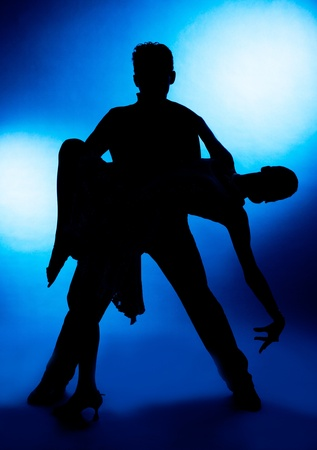 A silhouette of a couple dancing, against blue studio background photo
