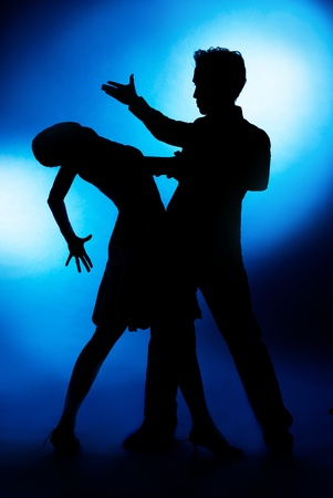 prom: A silhouette of a couple dancing, against blue studio background