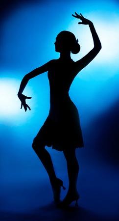 bailarina de flamenco: Una silueta de una mujer bailando delgado contra el fondo azul del estudio Foto de archivo