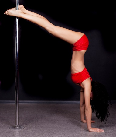 flex: Young sexy pole dance woman against dark background