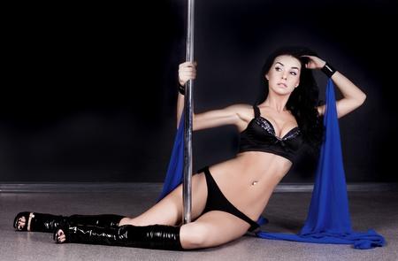 pole dance: Giovane donna sexy ballo pole su sfondo scuro