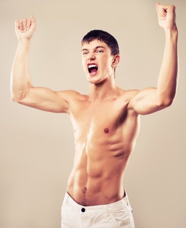screaming  young muscular man showing his biceps, isolated on brown background photo