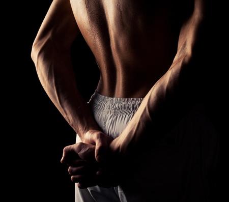 levantamiento de pesas: espalda y las manos de un joven musculoso, aislado contra el fondo negro del estudio