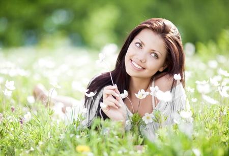 美しい若いブルネットの女性が暖かい夏の日の白い花を持つ、牧草地でリラックス