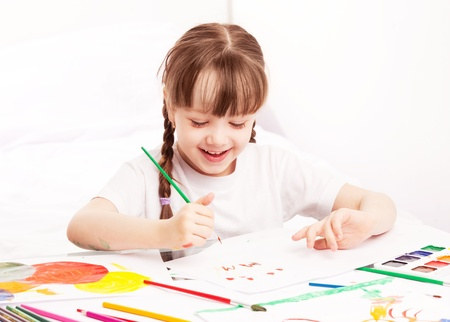 happy cute five year old girl sitting by the table and  painting with watercolor at home Stock Photo - 13046604