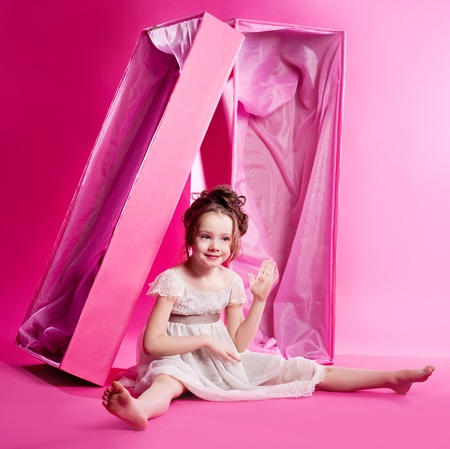 cute six year old girl photographed as an alive doll in the pink box,  against pink studio background