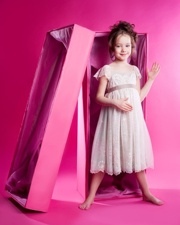 six girls: cute six year old girl photographed as an alive doll in the pink box,  against pink studio background
