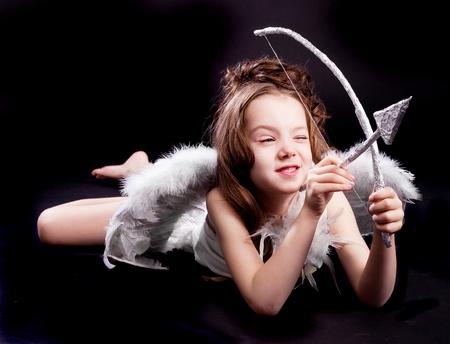 白い翼、弓と矢、黒のスタジオの背景に対して隔離されるキューピッドに扮したかわいい 6 歳女の子