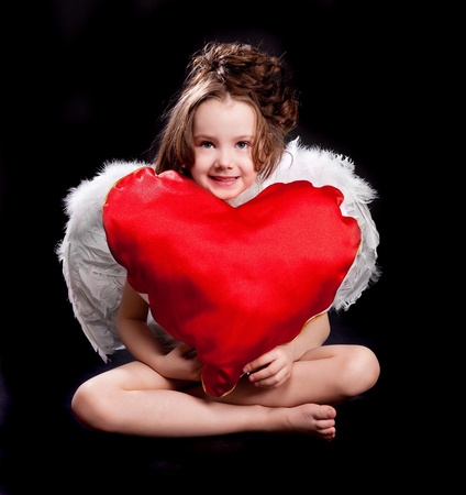 6 year old: cute  six year old girl  with white wings and a big heart  isolated against black studio background