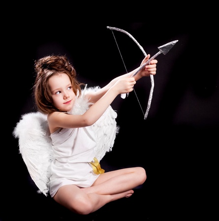 six girls: cute  six year old girl  dressed as a cupid with white wings, bow and arrow, isolated against black studio background