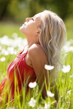 暖かい夏の日に白い花を持つ、草原に太陽を楽しむ美しい若いブロンドの女性