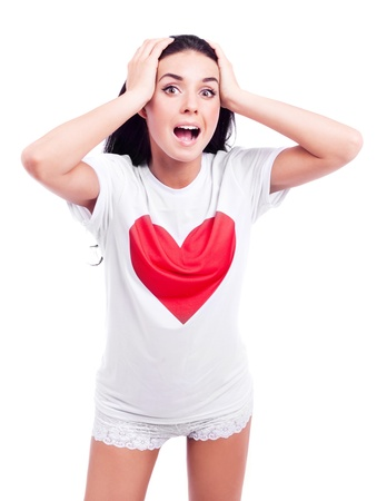 surprised young woman wearing a T-shirt with a big red heart and stretching hands to us, isolated against white background Stock Photo - 13077842