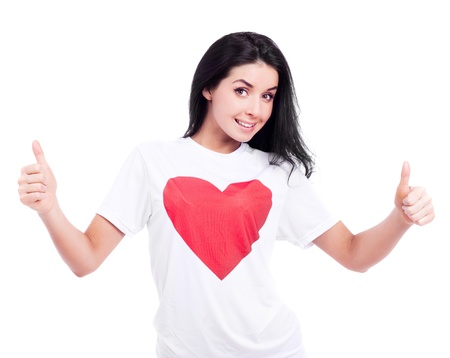 excited young woman wearing a T-shirt with a big red heart and  and showing two thumbs up, isolated against white background photo