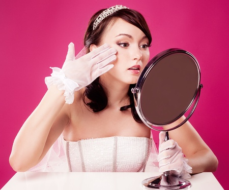 woman in the mirror: worried bride, sitting by the table with a mirror, isolated against pink studio background