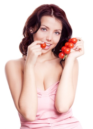 petite: portrait of a young beautiful brunette woman eating cherry tomatoes, isolated against white background