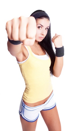 beautiful young brunette woman wearing sports clothes,  practicing fighting