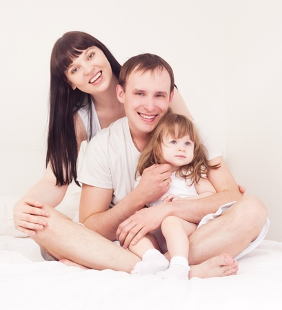 happy family; mother ,father and their baby in bed at home (focus on the man) photo