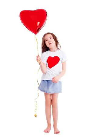 palloncino cuore: carino bambina di sei anni, con un grande cuore rosso a forma di palloncino, isolato su sfondo bianco