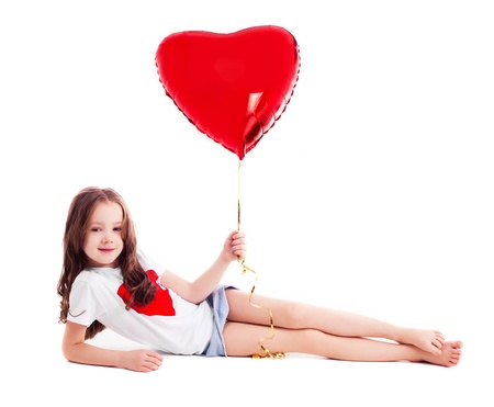 6 years: cute six year old girl  with a big red heart-shaped balloon, isolated against white background