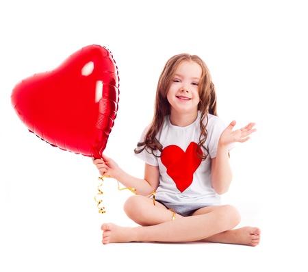 old year: carino bambina di sei anni, con un grande cuore rosso a forma di palloncino, isolato su sfondo bianco