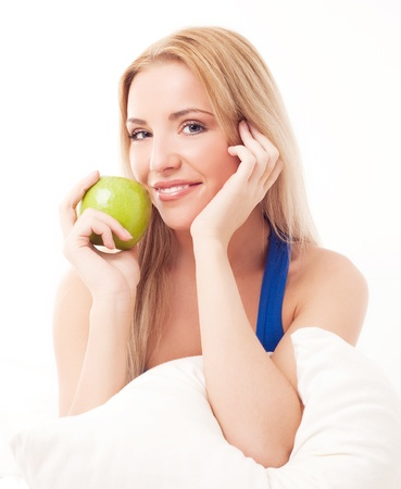 portrait of a happy beautiful woman in bed at home holding a green apple  Stock Photo - 13202245