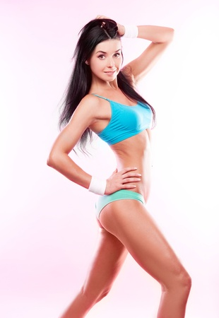 petite: beautiful sporty woman against pink studio background