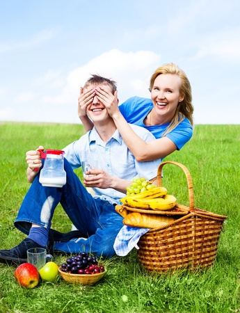 happy young couple having a picnic outdoor on a summer day photo