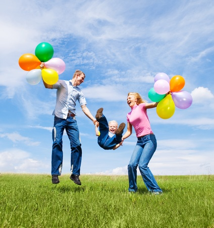happy family with balloons  jumping outdoor on a warm summer day Standard-Bild