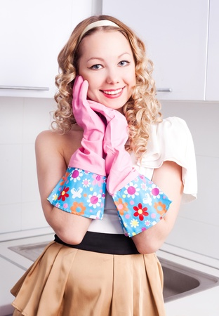 housewife gloves: beautiful young housewife wearing rubber gloves in the kitchen