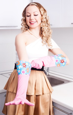 put up: beautiful young housewife putting on rubber gloves in the kitchen