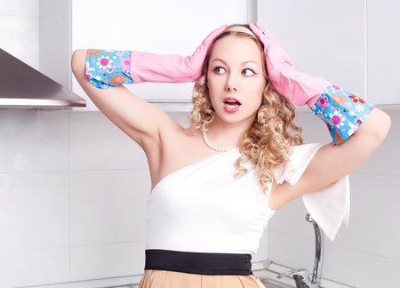 housewife gloves: beautiful surprised young housewife wearing rubber gloves in the kitchen at home