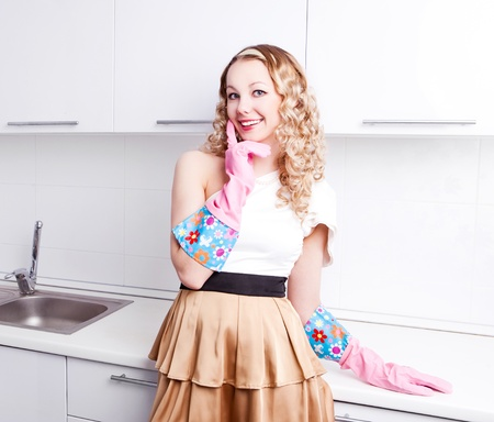 tidying up: beautiful young housewife wearing rubber gloves in the kitchen at home