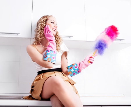 petite girl: beautiful young housewife wearing rubber gloves and holding a dust brush in the kitchen Stock Photo