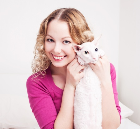 pet care: pretty young woman with her cat in bed at home
