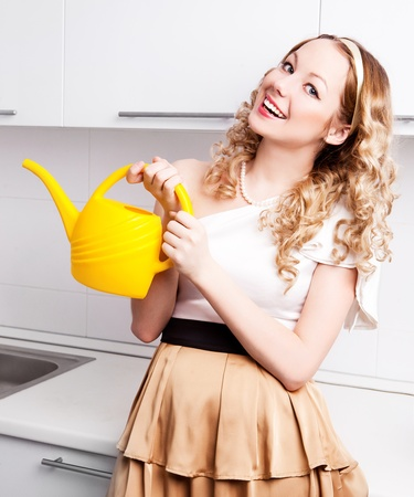 bailer: beautiful young housewife wearing rubber gloves in the kitchen