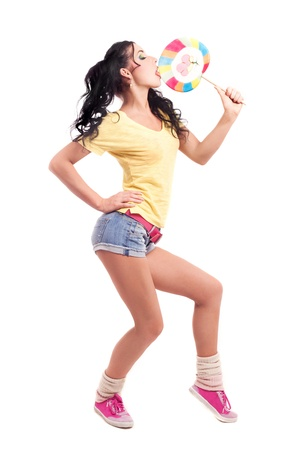pretty young brunette woman eating a candy, isolated against white background photo