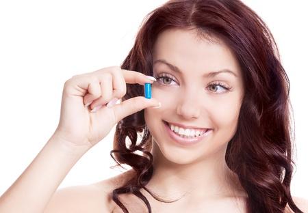 pills in hand: mujer bonita joven que sostiene una p�ldora azul, aislado contra el fondo blanco