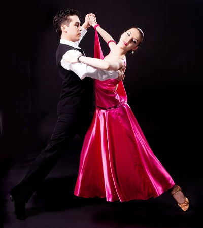 ballroom dancing: a couple dancing against black studio background