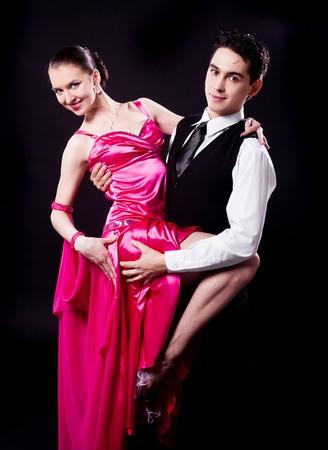 bailando salsa: una pareja de baile contra el fondo negro del estudio