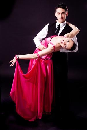 ballroom dance: a couple dancing against black studio background